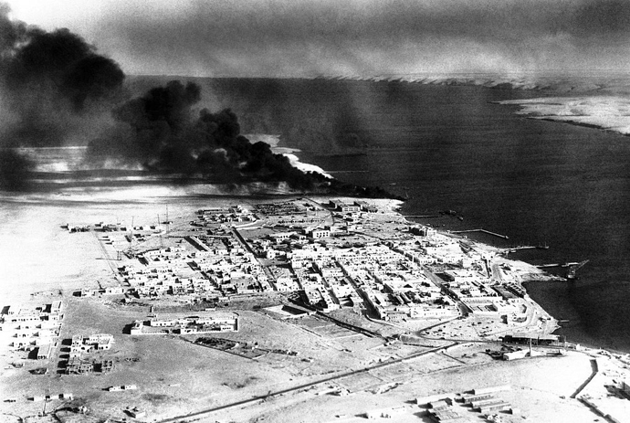 Photograph showing a costal African city with smoke billowing from one of the port/harbour areas