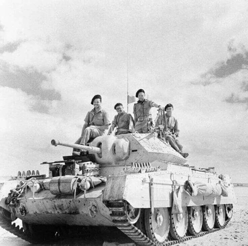 A picture of a World War 2 tank with the crew on top, at rest
