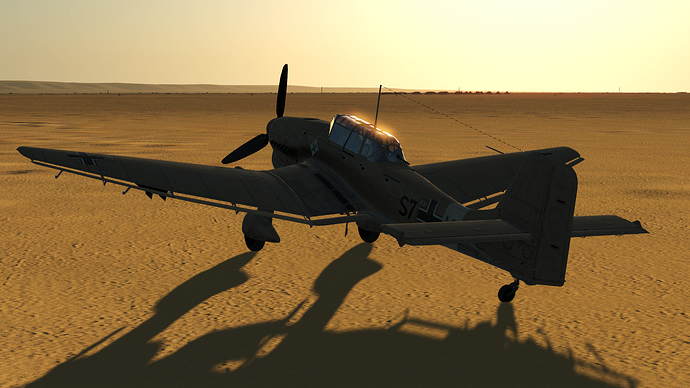 An in game screenshot of a Stuka, external from the back left as it sits at rest in the rising/setting sun.