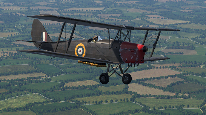 An in game screenshot of a Tiger Moth, external from the front right as it flies over the French country-side with a small bomb load.