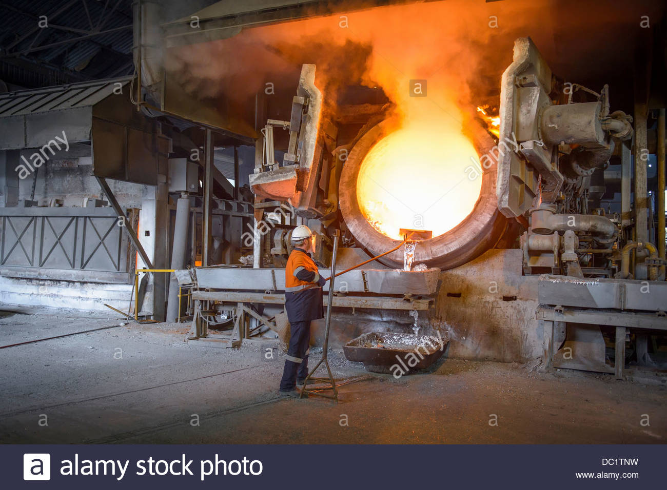 worker-raking-liquid-aluminum-from-furnace-at-recycling-plant-DC1TNW